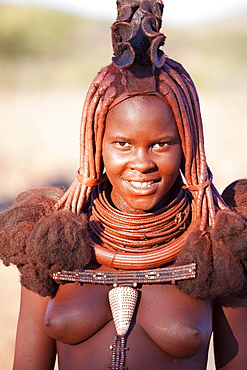 Young Himba woman wearing traditional dress and jewellery and with her skin covered in Otjize, a mixture of butterfat and ochre, Kunene Region, formerly Kaokoland, Namibia, Africa