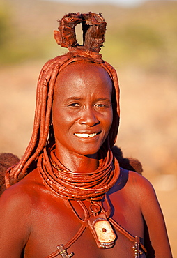 Himba woman wearing traditional leather clothing and jewellery, hair brading and skin covered in Otjize, a mixture of butterfat and ochre, Kunene Region (formerly Kaokoland) in the far north of Namibia, Africa