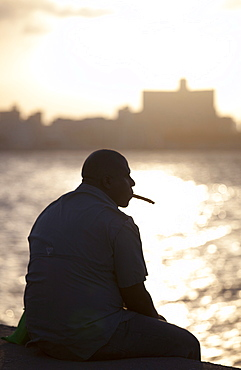 Man in semi silhouette sat on the sea wall at sunset, smoking a cigar, The Malecon, Havana Centro, Havana, Cuba, West Indies, Central America