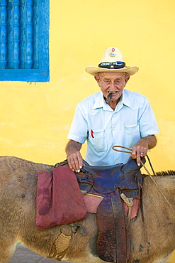 Portrait of old man wearing straw hat and smoking cigar, posing against a yellow wall with his donkey for tourist pesos, Trinidad, Cuba, West Indies, Central America