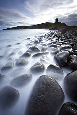 Long exposure to record motion in the sea as it washes around black basalt boulders on a beach at Embleton Bay with the silhouette of Dunstanburgh Castle in the distance, Embleton Bay, near Alnwick, Northumberland, England, United Kingdom, Europe