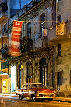 Street scene at night lit by artificial lighting with vintage American car and fluttering revolutionary banner, Havana Centro, Havana, Cuba, West Indies, Central America