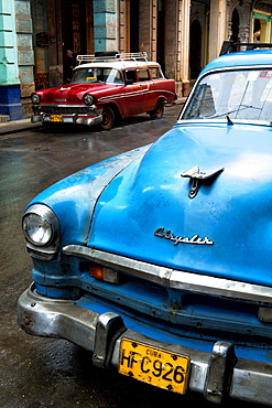 Vintage American cars parked on a street during early morning rainfall, Havana, Cuba, West Indies, Central America