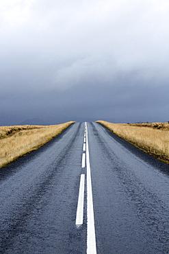 Road stretching away towards stormy sky, Snaefellsnes Peninsula, Iceland, Polar Regions
