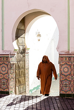 Local man dressed in traditional djellaba walking out of mosque in the Kasbah, Marrakech, Morocco, North Africa, Africa