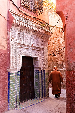 Local man dressed in traditional djellaba walking through street in the Kasbah, Marrakech, Morocco, North Africa, Africa
