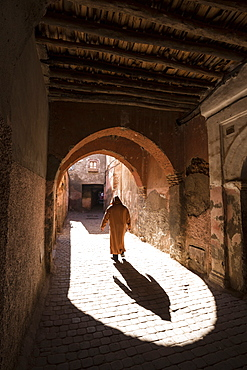 Local man dressed in traditional djellaba walking through archway in a street in the Kasbah, Marrakech, Morocco, North Africa, Africa