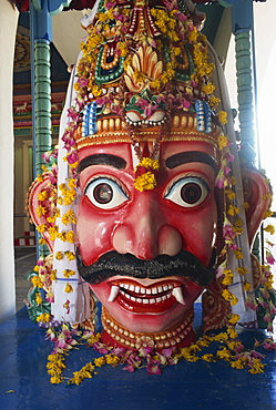 Close-up of statue with wide eyes and fangs at Sri Mariamman temple, a Hindu temple on Pagoda Road, Singapore, Southeast Asia, Asia