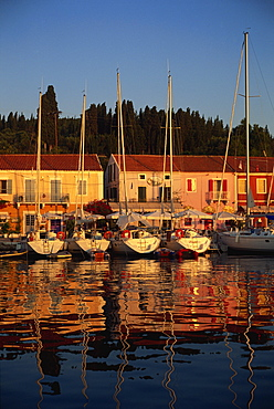 Reflections of boats in the evening at Fiskardo, on Kefalonia, Ionian Islands, Greek Islands, Greece, Europe