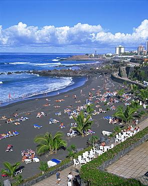 Tourists on volcanic sand beach at Playa Jardin, with San Felipe Castle and Hotel Puerto Playa beyond, at Puerto de la Cruz, Tenerife, Canary Islands, Spain, Atlantic, Europe