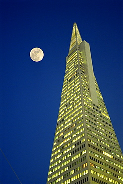 The Transamerica Pyramid, illuminated at dusk with full moon, designed by the architect William Pereira and built in 1972, San Francisco, California, United States of America, North America