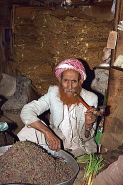 Portrait of an elderly shopkeeper with henna dyed beard, smoking a pipe, Djiblah, Yemen, Middle East