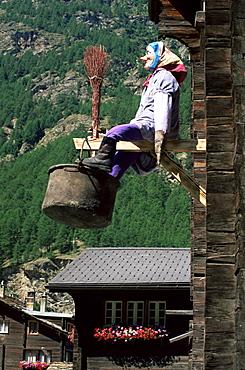 Witch hanging outside village house, Tasch, near Zermatt, Valais, Switzerland, Europe