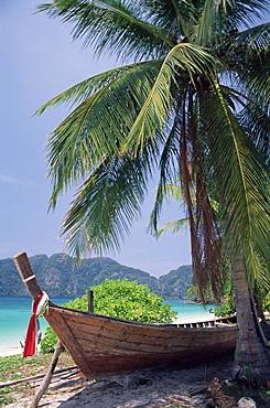 Wooden boat beneath palm trees on beach, Hin Phae Bay, Ko Phi Phi Don, off the island of Phuket, Thailand, Southeast Asia, Asia