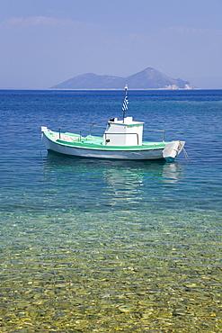 Small boat anchored offshore, the island of Atokos visible on horizon, Kioni, Ithaca (Ithaki), Ionian Islands, Greece