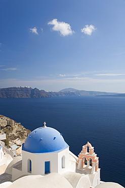 Typical church clinging to hillside above the Aegean Sea, Oia (Ia), Santorini (Thira) (Thera), Cyclades Islands, Greek Islands, Greece, Europe