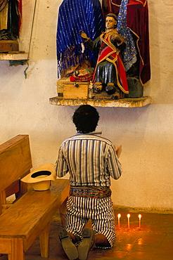 Man in traditional dress praying to Jesus, Santiago Atitlan, Guatemala, Central America
