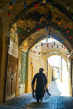 Mullah hurrying down typical vaulted alleyway, Yazd, Iran, Middle East