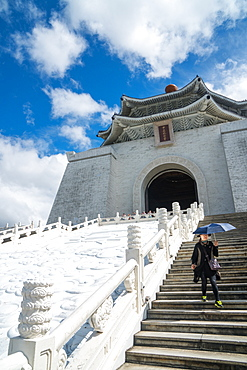 Woman with sun-shielding umbrella coming down the steps which lead up to the Chiang Kai-Shek Memorial Hall, Taipei, Taiwan, Asia