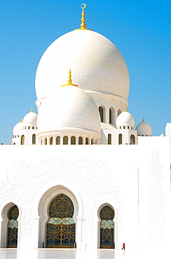 Interior of Sheikh Zayed Grand Mosque, brilliant white of marble buildings punctuated by tiny woman in red, Abu Dhabi, United Arab Emirates, Middle East