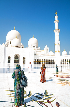 Tourists, fully covered as required by religious rules, photographing the interior of Sheikh Zayed Grand Mosque, Abu Dhabi, United Arab Emirates, Middle East
