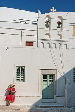 Woman in red dress and straw hat on white stone ledge outside the church, Kastro Village, Sifnos, Cyclades, Greek Islands, Greece, Europe