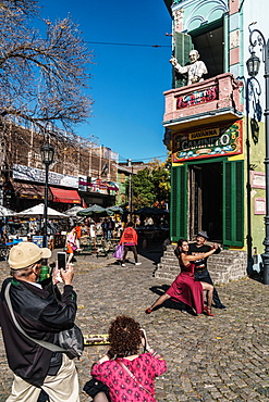 Street tango dancer hamming it up with tourists outside a bar on the corner of El Caminito, La Boca, Buenos Aires, Argentina, South America