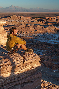 Happy hiker enjoying the view at sunset across Death Valley, near San Pedro de Atacama, Chile, South America