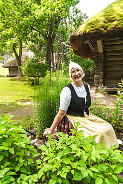 Woman in traditional dress outside a 17th century farmstead, Latvian Ethnographic Open Air Museum, Riga, Latvia, Europe
