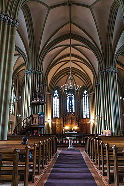 Nave of St. Gertrude Old Church, worshipper in pew, Riga, Latvia, Europe