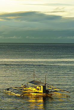 A lone bangka (outrigger canoe) bathed in warm dawn light berthed by Panglao Beach, Bohol Island, Philippines, Southeast Asia, Asia