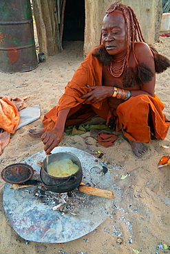 One senior red ochred Himba woman cooking her meal on an open fire, Puros Village, near Sesfontein, Namibia, Africa
