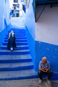 Woman in dark blue traditional clothes climbing up the stairs of alleyway, man seated in the foreground, Chefchaouen, Morocco, North Africa, Africa