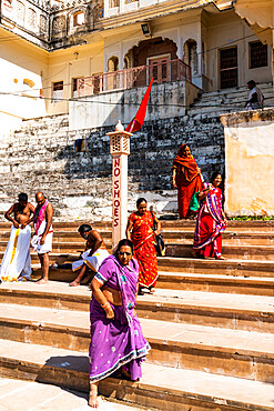 Women in brightly coloured saris walking down the ghats (steps down) barefoot to the sacred water of Pushkar Lake, Pushkar, Rajasthan, India, Asia