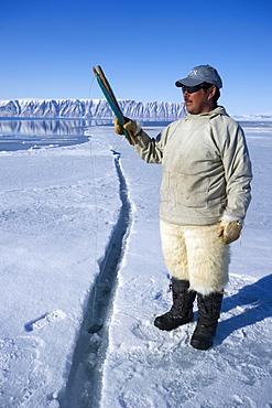 Inuit hunter line fishing at the floe edge for Arctic cod, sculpin and halibut near Herbert Island, Greenland, Denmark, Polar Regions - 465-3397