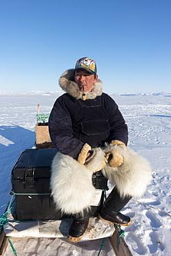 Inuit hunter smoking a pipe on the sea ice near Herbert Island, Greenland, Denmark, Polar Regions