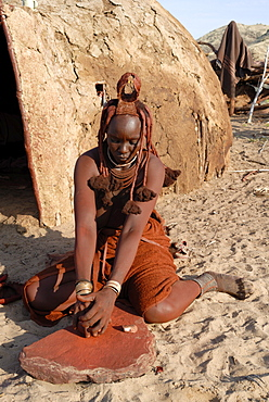 Woman of the Himba tribe grinding pigment for body decoration, Kaokoland, Namibia, Africa