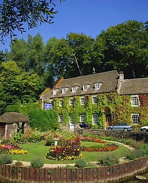The Swan Hotel and garden full of summer flowers at Bibury, in the Cotswolds, Gloucestershire, England, United Kingdom, Europe
