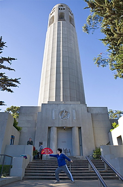 Coit Tower with a Chinese woman performing tai chi fan, San Francisco, California, United States of America, North America