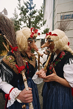Two people wearing masks and traditional dress, one carrying a broomstick, in the Fasnacht carnival in Imst, Austria, Europe