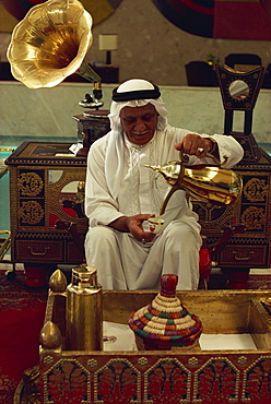 Elderly man in traditional dress pouring drink, Bahrain, Middle East