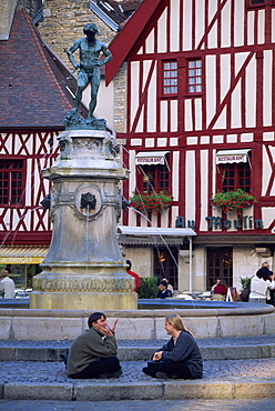 A couple sit in front of a fountain in the Place Francois Rude, with half timbered houses behind, in Dijon, Burgundy, France, Europe