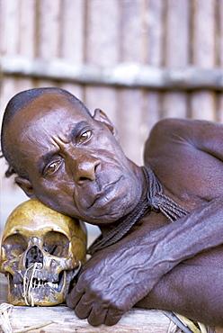 Portrait of an Asmat tribesman leaning on a human skull, Irian Jaya (West Irian) (Irian Barat), New Guinea, Indonesia, Asia