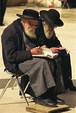 Two old Orthodox Jews sitting praying at the Western or Wailing Wall in the Old City of Jerusalem, Israel, Middle East
