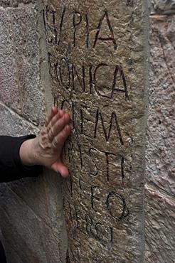 Pilgrim's hand caressing the stone at Station VI on the Via Dolorosa during Good Friday Catholic procession, Old City, Jerusalem, Israel, Middle East