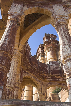 Palace towers of Meherangarh fort seen through remains of a stone temple, Jodhpur, Rajasthan state, India, Asia
