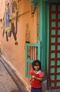 Small girl standing in doorway of typical house decorated with Mewar folk art, Jagdish Mandir area, old city, Udaipur, Rajasthan state, India, Asia
