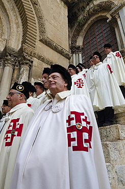 Members of the Order of the Holy Sepulchre pausing in full dress at the Holy Sepulchre, Jerusalem Old City, Israel, Middle East