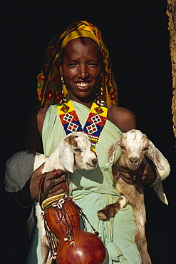 Woman holding twin kid goats and gourd, and wearing beads, Harar, Ethiopia, Africa