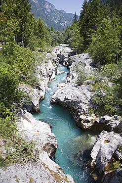 Soca River with clear emerald water flowing between eroded rocks in Trenta Valley in summer, Triglav National Park, Julian Alps, Slovenia, Europe